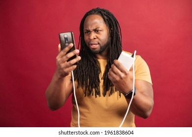 Disappointed African American guy with dreadlocks standing isolated on red wall, holding discharged mobile phone connected to power bank through USB cable, trying to charge smartphone unsuccessfully
