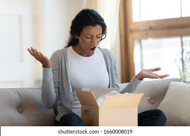 Disappointed African American young woman sit on couch feel confused with wrong order shopping online, mad biracial millennial female frustrated by Internet purchase bad quality, delivery concept