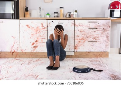 Disappointed African Woman Sitting On Kitchen Floor With Spilled Food In Kitchen