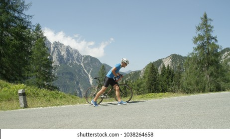 Disappointed athletic bike rider pushes his road bicycle up sunny mountain road. Pro road cyclist quit grueling mountain pass race and decided to walk the rest of the way. Picturesque sunny mountains
