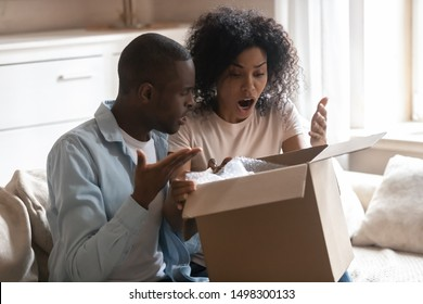 Disappointed biracial husband and wife unpack cardboard box get wrong order, frustrated african American client couple open unbox delivery package, feel confused receive bad quality, damaged product
