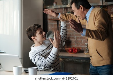 Disappointed boy arguing with his father