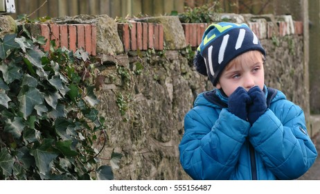 Disappointed boy standing in front of a stone wall feeling cold and tired