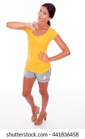 Disappointed brunette woman gesturing a thumbs down in front while looking at camera and wearing a yellow t-shirt and short jeans isolated