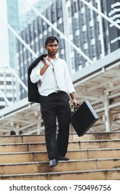 Disappointed businessman walking down the stairs in city. And holding a briefcase and suit jacket. Image of Stressed businessman concept.
