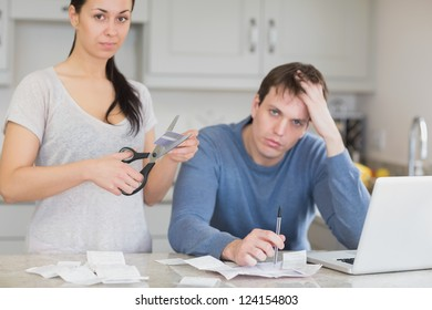 Disappointed couple in the kitchen cutting credit card and looking at finances on laptop