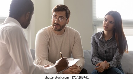Disappointed couple at reception with family therapist. African american doctor listening man in bad mood. Family relationship disorder concept. Psychology session with coach