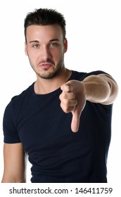 Disappointed or displeased attractive young man doing thumb down sign, isolated on white
