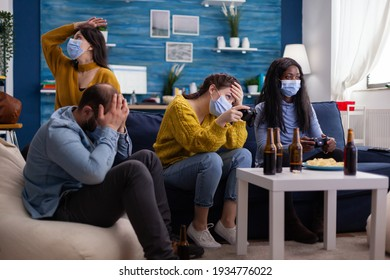 Disappointed diverse group of people playing video games respecting social distancing because of orona outbreak wearing face mask not to spread the virus and get sick. Beer bottle and chips.