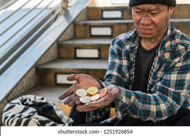Disappointed face expression of a  male homeless beggar with the handful of bitcoin coins  - devaluation of bitcoin concept