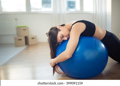 Disappointed fitness woman sitting on fitness pilates ball in room after work.Trying to work out exercise yoga and pilates.Discouraged,fitness disappointment with the progress.Tired lazy woman