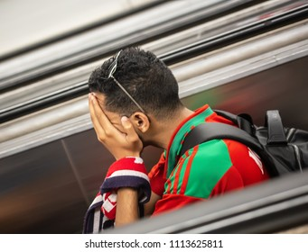 Disappointed football fan of Morocco after FIFA world cup match with Iran in St Petersburg Russia 2018 June 15. Loss 0 - 1. The man sins on the stairs of subway escalator closing his face with a palm