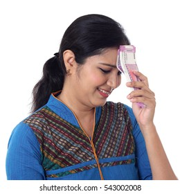 Disappointed Indian woman holding 2000 rupee notes
