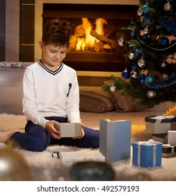 Disappointed little boy sitting with present box on floor, looking sad.