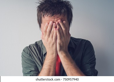 Disappointed man crying with head in hands. Sad and lonely adult male hiding tears.