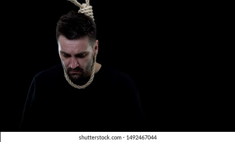 Disappointed man in rope noose on black background, life crisis, depression