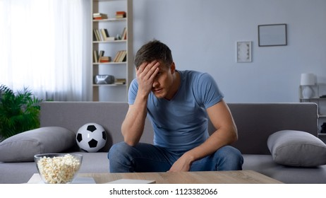 Disappointed man shocked by defeat of favorite football team on championship