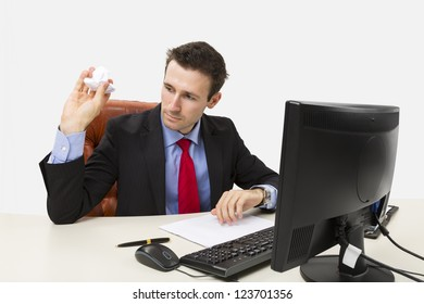 Disappointed manager throwing a crumpled paper in front of his computer at office.