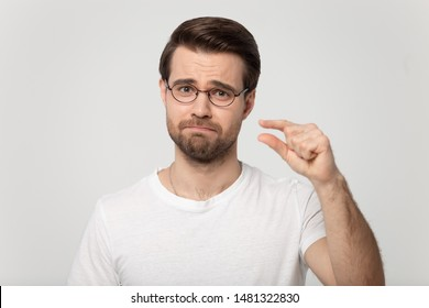 Disappointed millennial man in glasses showing small size length with a pity, isolated on grey white studio background. Head shot portrait young guy looking at camera showing measurement with fingers.