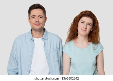 Disappointed millennial man and woman in casual clothes isolated on grey studio background unhappy hearing bad news, upset guy and girl feel down or sad, have problems or unpleasant life experience