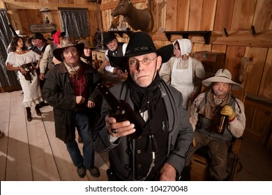 Disappointed sheriff holds empty bottle in old west tavern