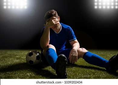 Disappointed soccer player in blue sitting on pitch after losing the match