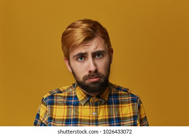 Disappointed unshaven male feels upset. Feel lonliness and sad. Has regretful expression. Dyed blonde gold hair. Isolated over studio yellow background.