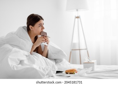 Disappointed upset millennial woman eating chocolate bar on bed with fast food at home, suffering from overeating. Mental problems, stress, depression, substitution, eating disorder and food addiction