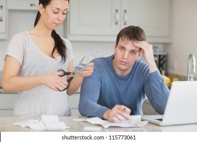 Disappointed woman cutting through a credit card with stressed husband in kitchen