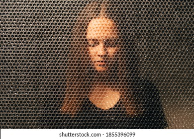 Disappointed woman. Family abuse. Social pressure. Betrayal loss. Textured art portrait of exhausted unhappy sad suffering lady in black with closed eyes in darkness behind plastic bubble wrap.