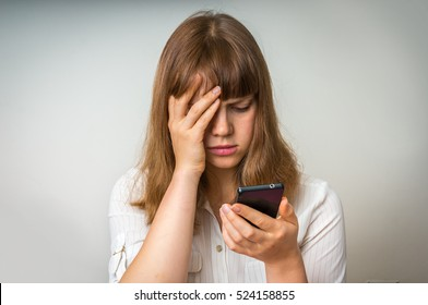 Disappointed woman holding and looking on mobile phone, she is disgusted and shocked with received message