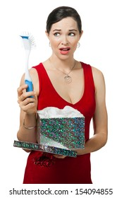 A disappointed woman looks at dish brush gift. Isolated on white.