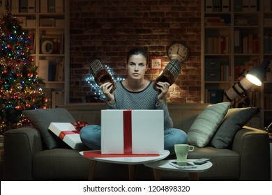 Disappointed woman receiving a dissatisfying Christmas gift: she is holding a pair of ugly slippers