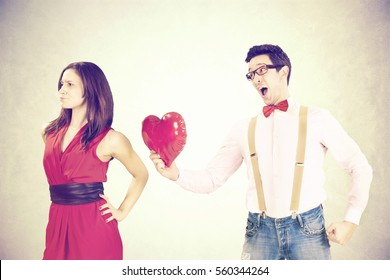 disappointed woman rejecting the red heart of her boyfriend in a Funny Valentine's Day