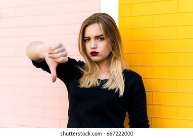 Disappointed woman standing on bright brick background and showing thumbs down. The modern concept of gestures, symbols, signs. Negative emotion.