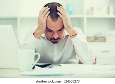 Disappointed worker at his office table feeling stressed, thinking and looking down