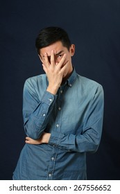 Disappointed young Asian man covering his face by palm and looking at camera