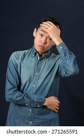 Disappointed young Asian man covering his forehead by palm and looking at camera