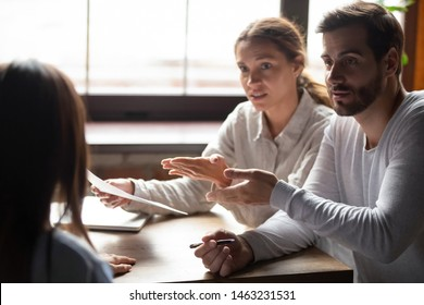 Disappointed young couple meeting with realtor or designer dispute complain about contract regulations, dissatisfied spouse clients have argument with banker blame specialist in incompetence