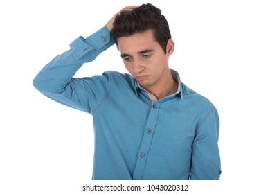 A disappointed young man looking down putting a hand on the head, isolated on a white background.