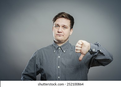 disappointed young man showing thumb down sign