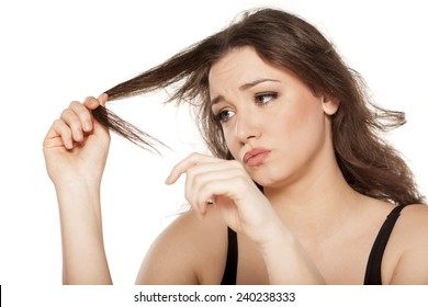 disappointed young woman looks at the tops of her hair