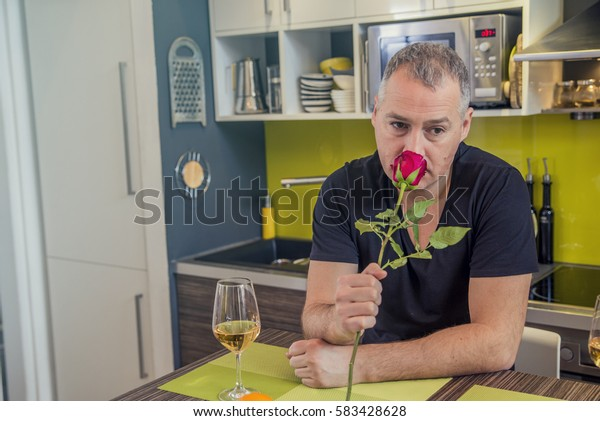 Disappointment and depression. Unrequited love concept. Young worried disappointed man with single red rose and vine waiting for his girlfriend.