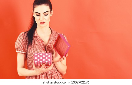 Disappointment and emotions concept. Woman opens gift box and feels disappointment.