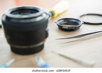 Disassemble & repair process of professional modern digital single reflex camera lens.Service center specialist repairing camera lenses with tools.Disassembled broken dslr lens
