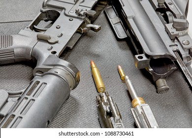 A disassembled AR15 rifle laying on a table with a 22 mm cartridge adaptor and a 5.56mm bullet