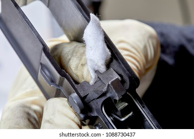 A disassembled AR15 rifle parts being cleaned with a cotton patch
