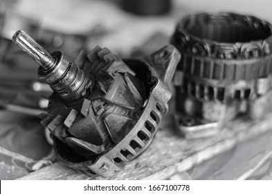 Disassembled car generator on a workbench. Stator and rotor of a used generator. Auto repair shop or service center. Eye level shooting. Selective focus. Black and white photo