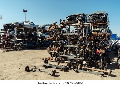 Disassembled car stock/Piles of used cars disassembled with wheels axels on the front row and car bodies in the backdrop.
