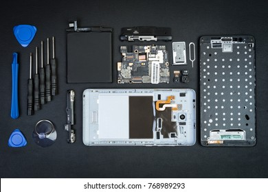 The disassembled cell phone with the removed screen and special purpose tools on the black desktop. Smartphone details. Workplace of the repairman of phones